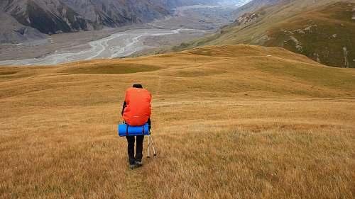 human person walking on mountain field
