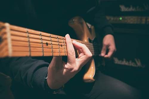 human person wearing black shirt paying guitar in closeup photography person