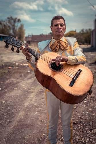 human standing man holding brown sting musical guitar during daytime person