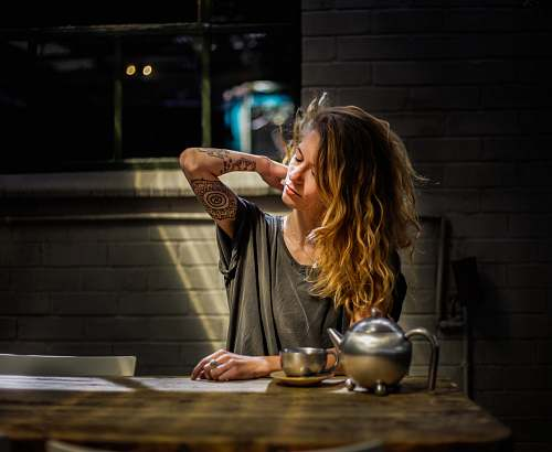 human woman in gray top sitting beside gray tea pot and cup on brown wooden table tattoo