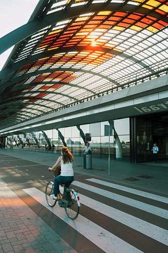 person woman riding beach cruiser bicycle on pedestrian lane human