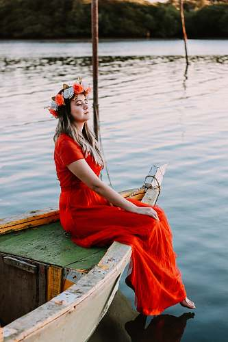 person woman sitting on boat in body of water while closing her eyes human
