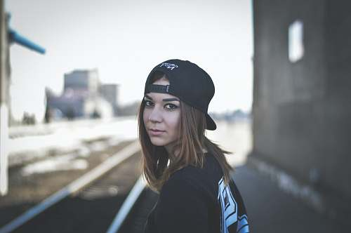 human woman wearing black snapback cap looking back person