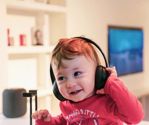 human baby listening in black headset people