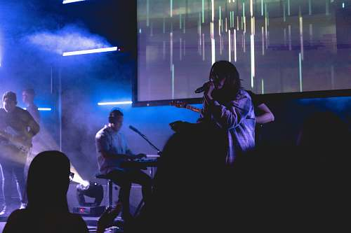 human boy singing with microphone beside man playing guitar, near man playing electronic keyboard, and man playing bass guitar on stage musician