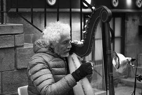 human grayscale photo of man playing harp near stairs black-and-white