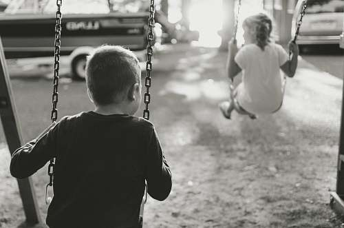 swing grayscale photography of boy and girl on swing toy