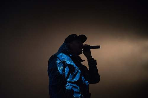 human man holding microphone low light photography music
