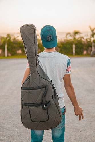 human man looking at green trees carrying grey guitar case people