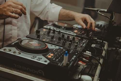 human man operating DJ controller dj