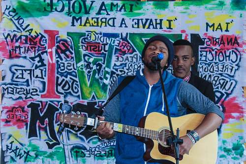 human man playing acoustic guitar while singing people