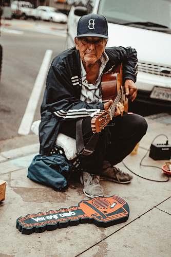 human man playing guitar while sitting people