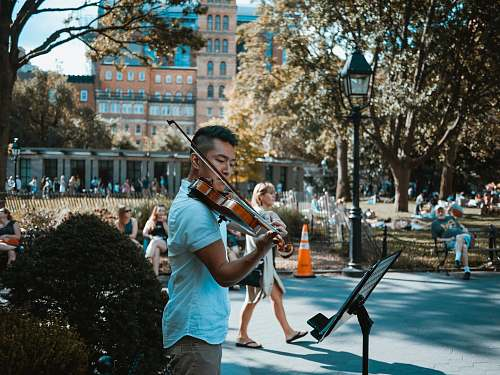 human man playing violin at the park people