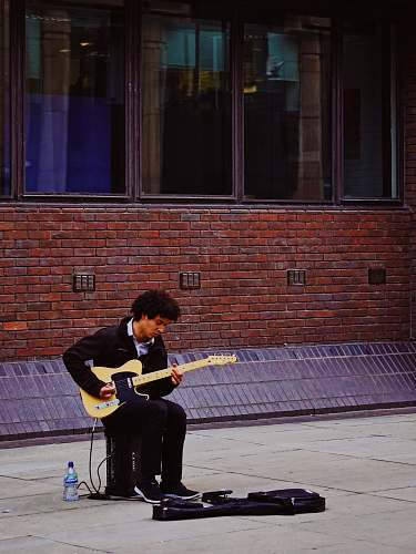 human man playing with his electric guitar while sitting on guitar amlplifier people
