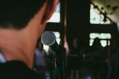 human man standing in front of microphone people