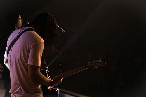human man standing while playing guitar people