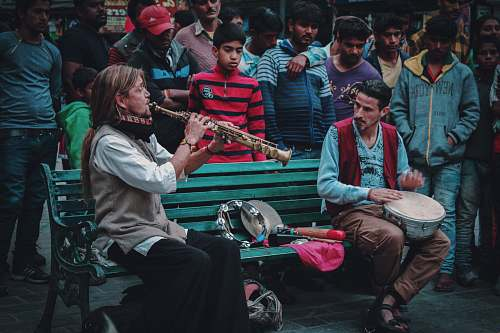 human people gathering looking at the man sitting on bench playing wind instrument people