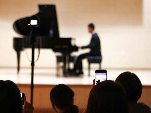 human person taking photo of person playing piano on stage people