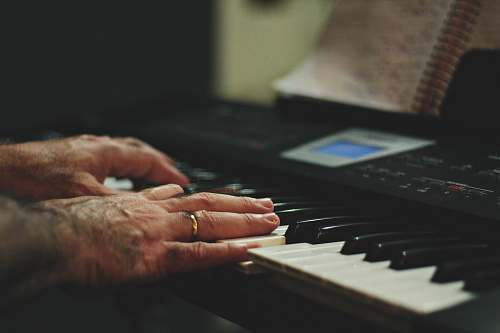 human shallow focus photo of person playing piano keyboard