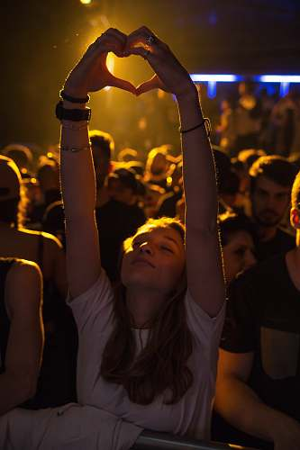 human woman at crowd raising her hand while making heart sign people