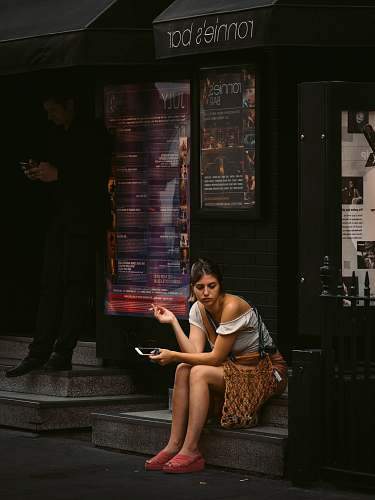 human woman holding smartphone sitting on Ronnie's Bar store people