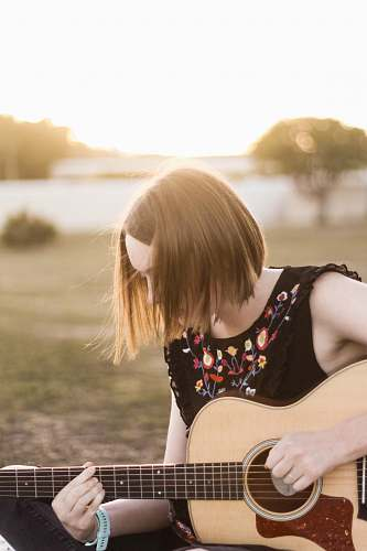human woman playing acoustic guitar people