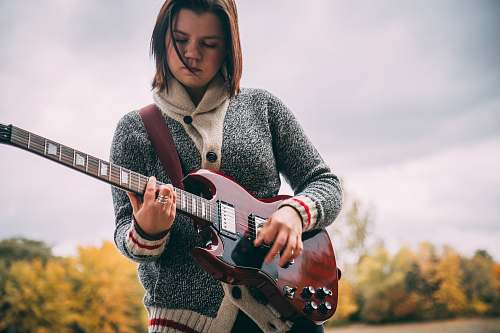 human woman playing guitar during daytime people