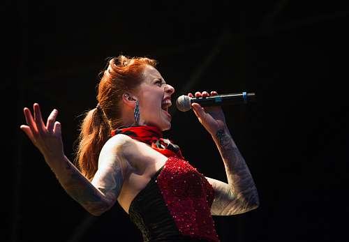 human woman singing on wireless microphone people