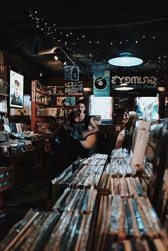 human woman sings while playing guitar people