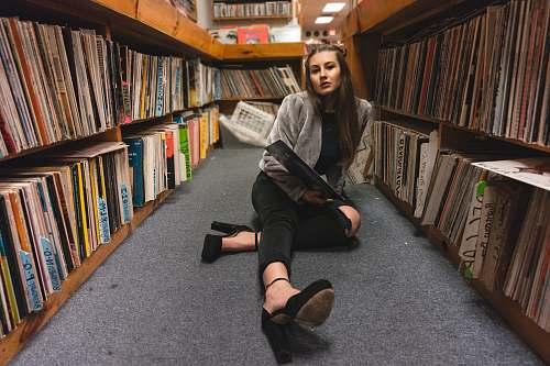 human woman sitting on floor between bookshelves people