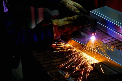 light man holding welding torch sparks