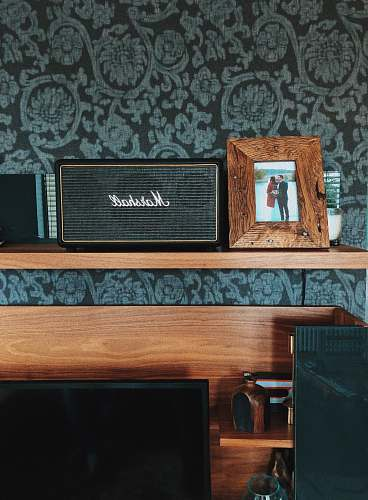 hardwood black Marshall speaker beside photo frame plywood
