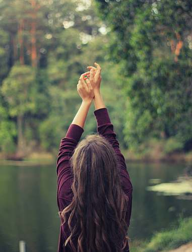 people woman raising both of her hands nature