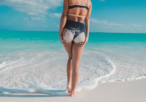 beach back view photography of woman in black bikini walking towards the sea bikini