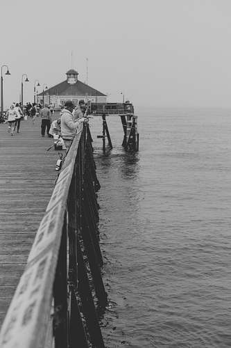 person Black and white photograph of people fishing on a pier at Imperial Beach black-and-white