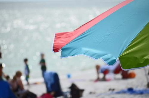 person blue, red, and green beach umbrella in closeup shot umbrella