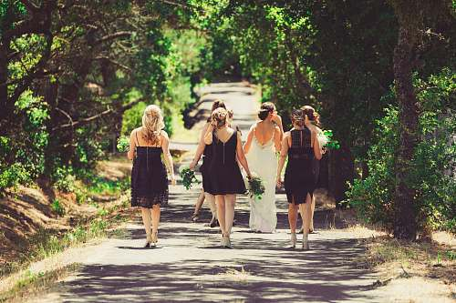 human bride and bridesmaid walking on street between green trees wedding