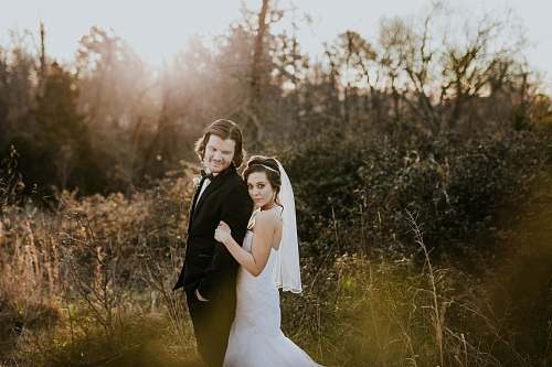 person bride and groom near green leafed plants during daytime wedding