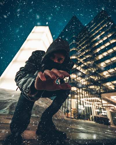 person close-up photography of man kneeling on ground front of gray high-rise building during snow weather human