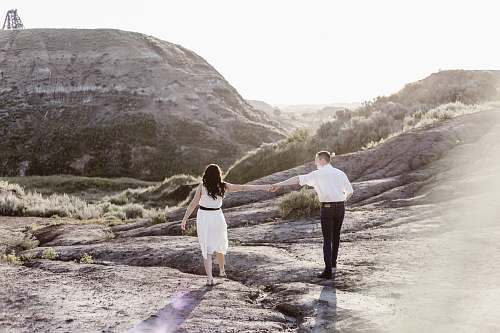 person couple holding hands while walking along the rocky coastline couple