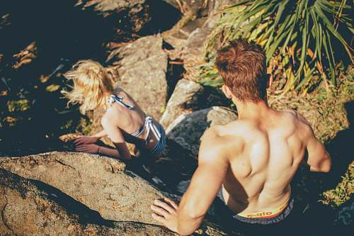 person Couple in swimwear climbing down the rocky cliff at Kings Beach woman