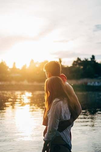 couple couple walking on lake side watching sunset close-up photo summer