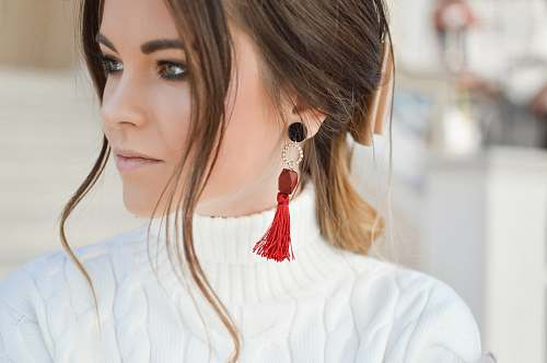 person focus photography of woman wearing red tassel earrings while looking on her left side human