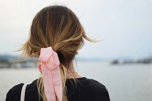 woman focus photography of woman with pink hair bow facing on body of water hair