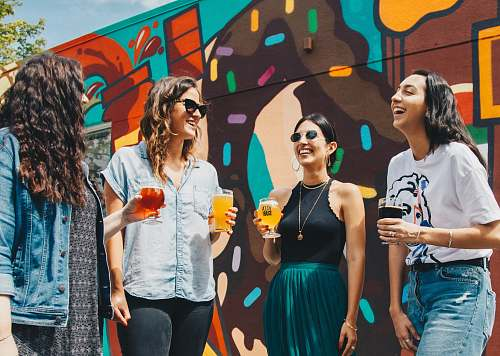 person four women holding drinks while laughing together during daytime human