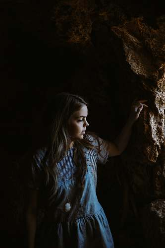 girl girl wearing blue and white dress holding on brown rocks cave