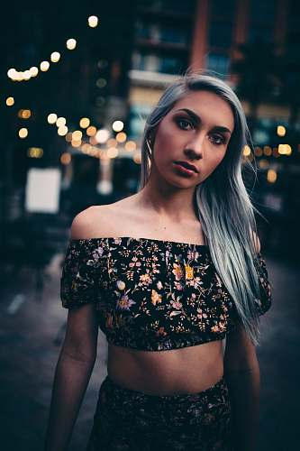 human gray haired woman wearing black-and-multicolored floral 2-piece crop dress person