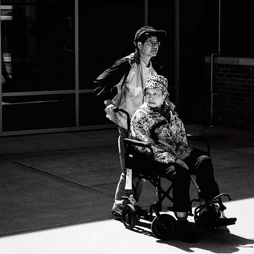 black-and-white gray scale photo of man pushing wheelchair wheelchair