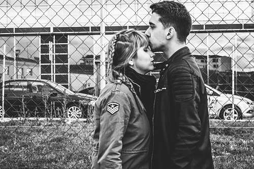 human grayscale photo of man kissing forehead of woman near fence black-and-white