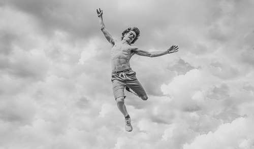 person grayscale photo of person jumping overlooking clouds black-and-white